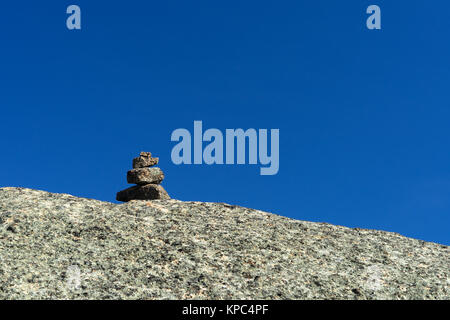 Rock cairn on a granite slab against a deep blue sky, Mount Jay, Adirondacks, USA. - Stock Photo