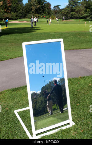 Golfers practicing on a driving range, seen in a mirror used for lessons. - Stock Photo