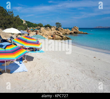 People at idyllic beach with turquoise colour sea and granite rocks at Capriccioli, Costa Smeralda, Sardinia, Italy, - Stock Photo