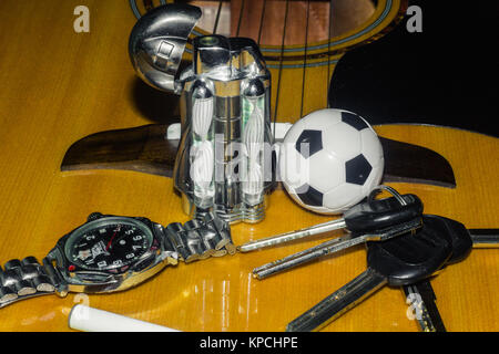 Wrist watch, cigarette, lighter, keychain with keys and acoustic guitar in the background - Stock Photo
