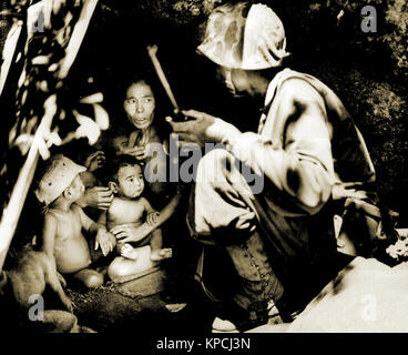 A member of a Marine patrol on Saipan found this family of Japanese hiding in a hillside cave. The mother, four - Stock Photo