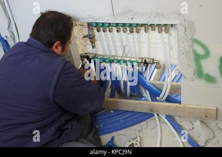 Construction site - worker manifold mounting thermal water system - Stock Photo
