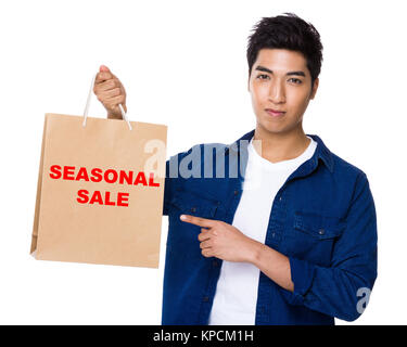 Asian mixed Indian man finger point to shopping bag for showing pharse of seasonal sale - Stock Photo