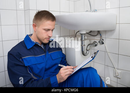 Young Plumber Writing On Clipboard - Stock Photo