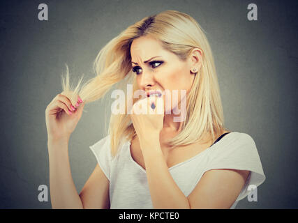 Young woman looking scared while exploring hair ends and biting fist. - Stock Photo
