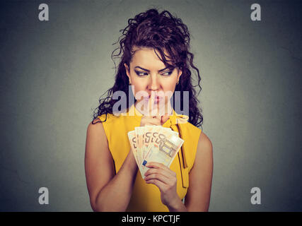 Woman holding pile of euros and asking for silence while practicing corruption. - Stock Photo