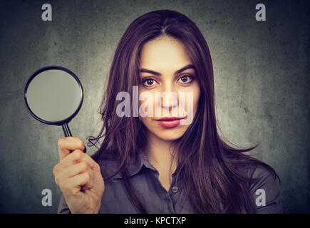 Young determined model holding magnifier and looking seriously at camera. - Stock Photo