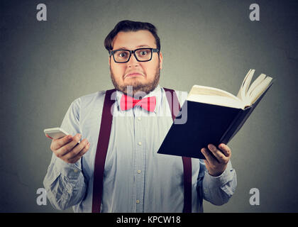 Chubby guy in glasses choosing between book and smartphone reading. - Stock Photo