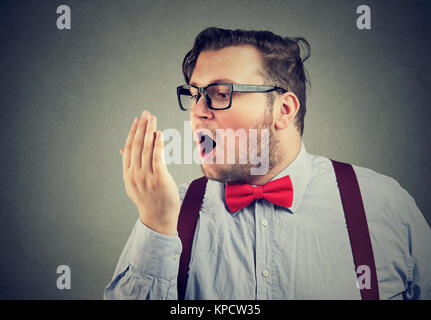 Bearded chubby man in glasses breathing on arm for breath test. - Stock Photo