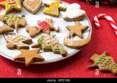 Concept image of Christmas fun with children - a variety of homemade gingerbreads on a red tablecloth in close-up. - Stock Photo