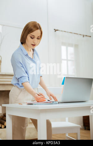 Alert blond woman doing her job from home - Stock Photo