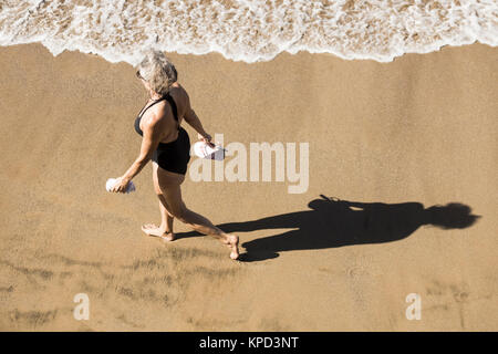 Mature woman in swimming costume walking on beach in Spain - Stock Photo