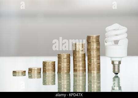 Fluorescent Light Bulb And Stacked Coins On Desk - Stock Photo