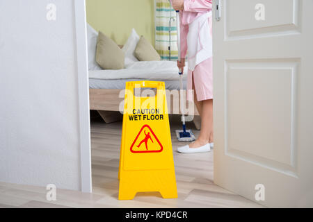 Female Housekeeper Cleaning Floor - Stock Photo