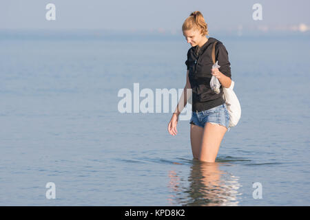 A girl walks along the beach and collect shells in the sea early in the morning - Stock Photo
