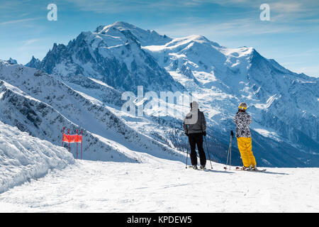 Skiers standing on a ski slope looking across to Mont Blanc in winter.  The male and female are wearing bright ski - Stock Photo