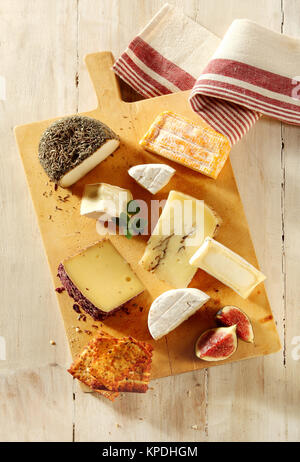 Assortment of soft and semi-hard cheeses on a cheeseboard with sliced fresh figs and toast for a gourmet appetizer - Stock Photo