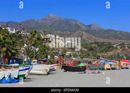 Fishing boats and tourist at Burriana Beach (Playa de Burriana) in Nerja on the Costa del Sol in the province of - Stock Photo
