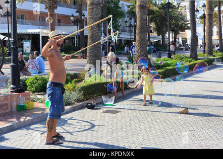 A small girl trying to catch a huge soap bubble made by an artistic performer at the Balcon de Europa in Nerja on - Stock Photo