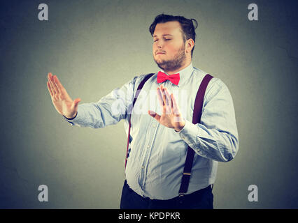 Blindfolded chubby man with eyes closed touching air. - Stock Photo