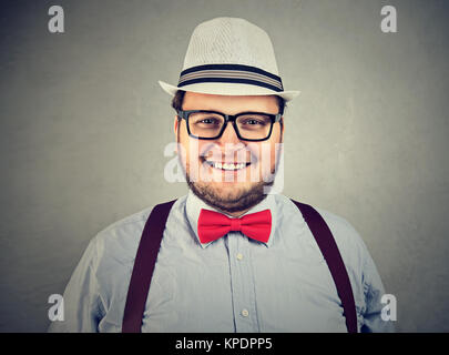 Portrait of cheerful chubby man in bow-tie and eyeglasses looking excitedly at camera. - Stock Photo