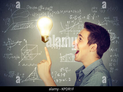 Side view of content man having great problem solution posing with burning light bulb. - Stock Photo
