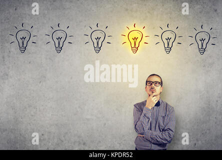 Young pensive man in eyeglasses looking up having brilliant idea. - Stock Photo