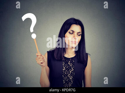 Young girl in black holding question mark looking confused about new information. - Stock Photo