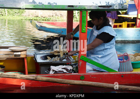 Xochimilco, Mexico City, Mexico - 2017: A woman on a trajinera (a local type of boat) cooks and sells local food - Stock Photo