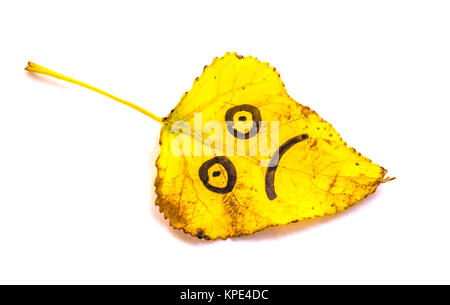 Yellow leaves with a picture of sad faces on an isolated white background - Stock Photo