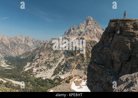 A hiker stands on a cliff in front of Grand Teton in Grand Teton National Park, Wyoming - Stock Photo