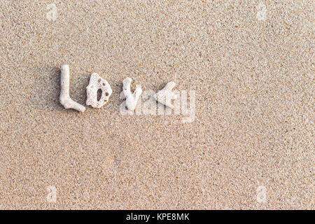 Love inscription made of shells on white sand - Stock Photo