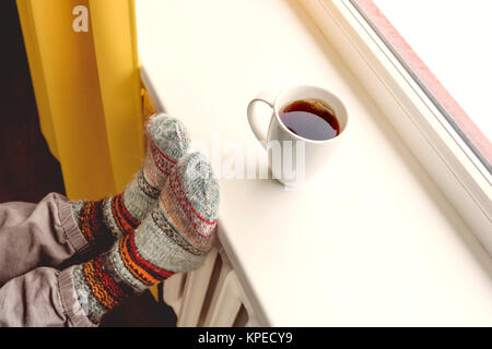 warming by the radiator and drinking hot tea - Stock Photo