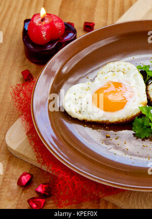 Heart-shaped fried egg on brown  plate.Valentine's Day breakfast. - Stock Photo
