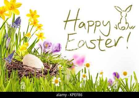 Happy Easter text surrounded by green grass, flowers and egg inside nest - Stock Photo