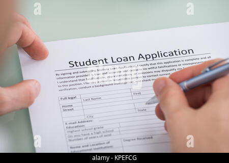 Person Hand Over Student Loan Application Form - Stock Photo