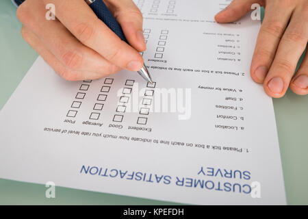 Person Hand Filling Customer Satisfaction Form - Stock Photo