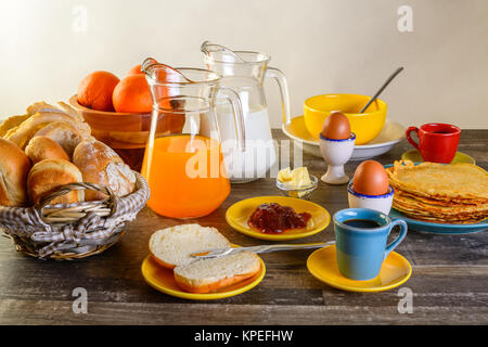 table of breakfast full set with eggs, pancakes, bread, jam ,juice and more - Stock Photo