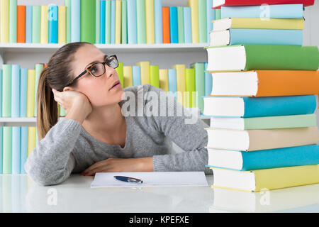 Contemplating Woman Sitting At Desk - Stock Photo