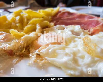 macro of fried eggs french fries and iberian ham - Stock Photo