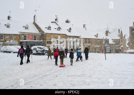 People walking through the market place at christmas time in the snow. Stow on the Wold, Cotswolds, Gloucestershire, - Stock Photo