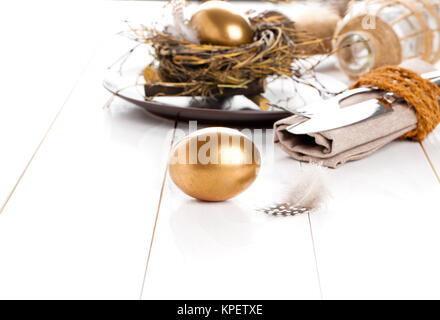 golden egg,table decoration on white wooden background - Stock Photo