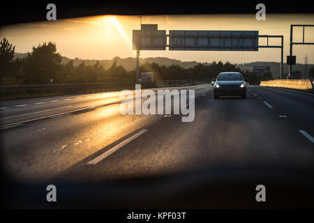 Cars on a highway at sunset - Stock Photo