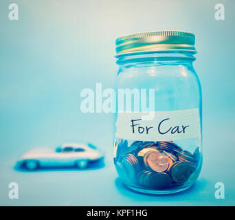 coins in bottle on blue background concept save money for car - Stock Photo