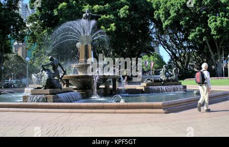 Tourists Outdoors Sydney Australia.  People or tourists in Australia walking past Archibald Memorial Fountain in - Stock Photo
