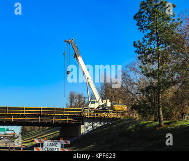 Large white mobile crane working on bridge above a highway with lane closed by tall pine tree and very blue sky - Stock Photo