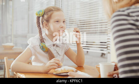 Little girl with mommy in cafe - teen explains something for mother - Stock Photo