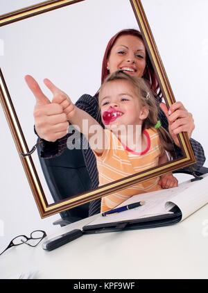 Symbolbild Karrierefrau und Mutter, erfolgreiche Geschaeftsfrau mit Tochter am Schreibtisch - sucessful businesswoman - Stock Photo