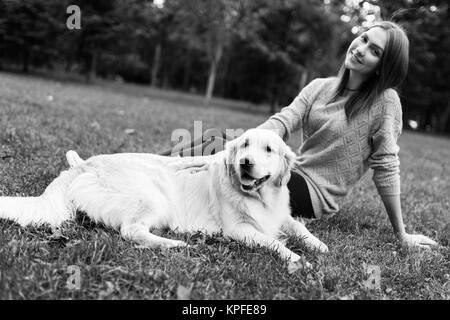 Black and white photo of brunette hugging labrador - Stock Photo