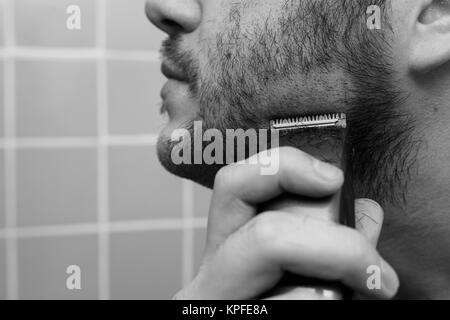 Portrait of young man shaving with trimmer - Stock Photo